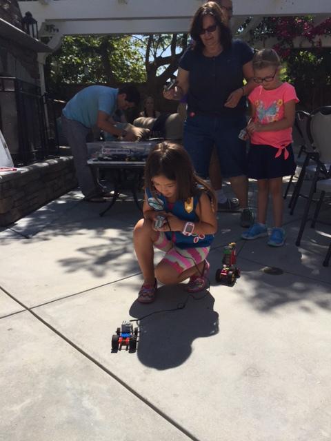 A Venture girl scout races her robotic car.